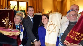 Rabbi Jason and Jodi Holtz carrying Torah scrolls rescued from the Czech Republic at a ceremony at Westminster Synagogue