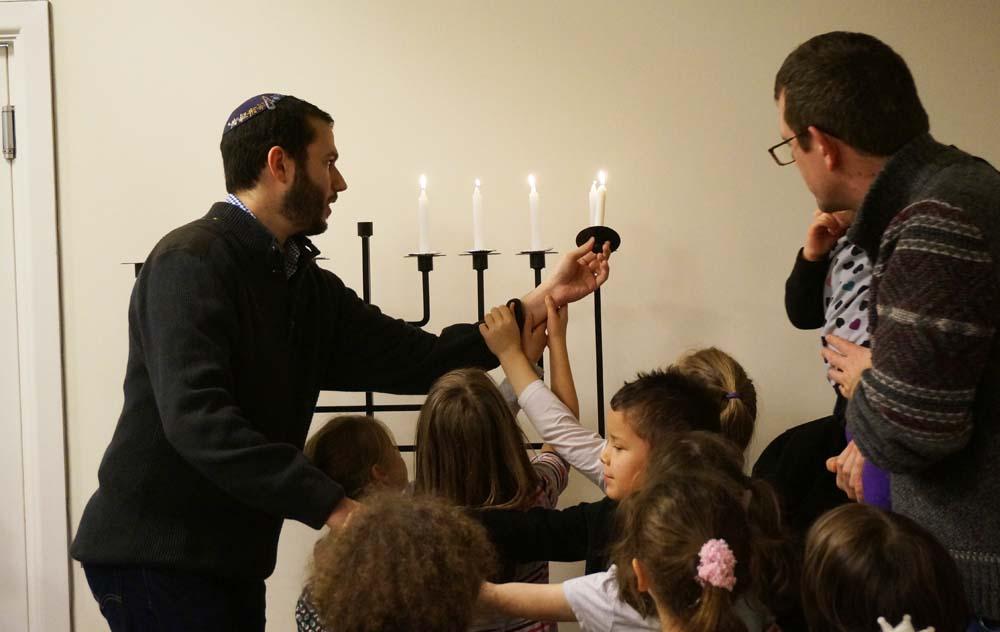 Helpiong_Rabbi_light_the_Menorah