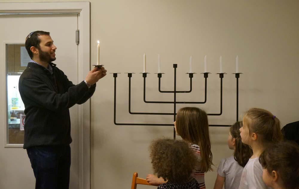Rabbi_holds_the_Shammas_candle